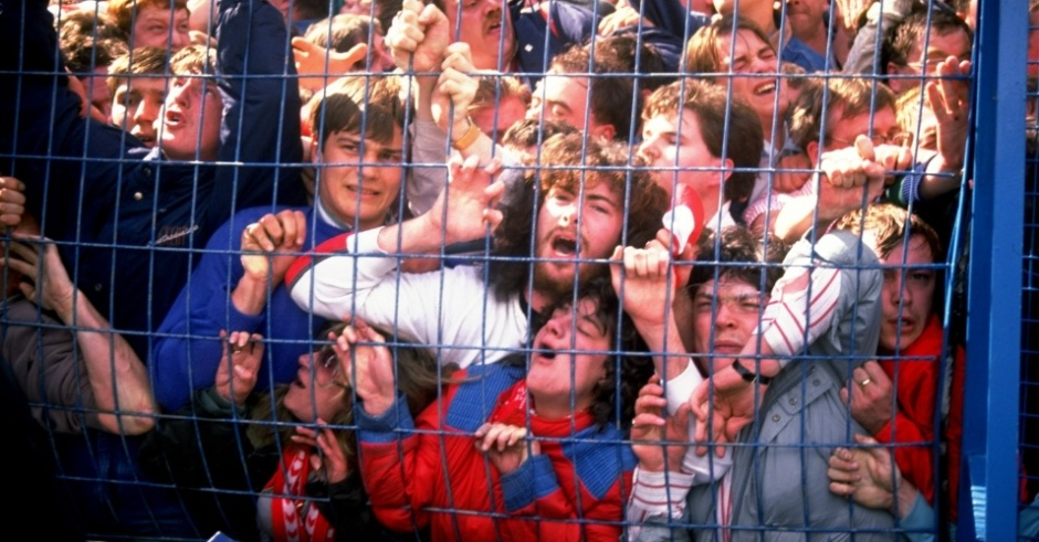 150489---torcedores-do-liverpool-ficam-presos-ao-alambrado-durante-a-tragedia-de-hillsborough-ha-25-anos-que-matou-96-torcedores-no-superlotado-estadio-de-hillsborough-em-sheffield-em-um-jogo-1397582586262_956x500
