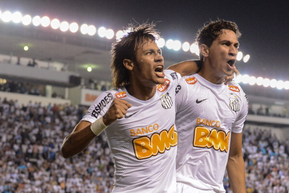 Footballer Neymar (L), of Brazilian team Santos, celebrates with teammate Ganso after scoring against Bolivia's Bolivar during a Libertadores Cup match at Vila Belmiro stadium in Santos, Brazil, on May 10, 2012. AFP PHOTO/Yasuyoshi CHIBA (Photo credit should read YASUYOSHI CHIBA/AFP/GettyImages)