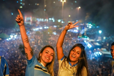 Fans of Brazil's Gremio cheer as they watch their team during the 2017 Copa Libertadores game against Argentina's Lanus on the streets of Porto Alegre, Brazil, on November 29, 2017. / AFP PHOTO / Jefferson BERNARDES