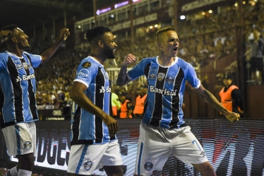 Brazil's Gremio forward Luan (R) celebrates with teammate forward Fernandinho (C) after scoring a goal against Argentina's Lanus during the Copa Libertadores 2017 final football match at Lanus stadium in Lanus, Buenos Aires, Argentina, on November 29, 2017. / AFP PHOTO / EITAN ABRAMOVICH
